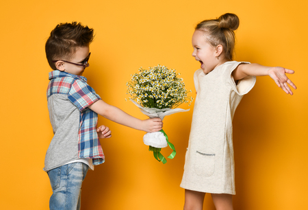 Foto de A little boy gives a bouquet of daisies to his girlfriend a girl. girl is happy to present and spread her arms wide to hug him. Concept of friendship, quarrel, date - Imagen libre de derechos