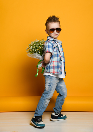Photo for Cute little boy holding a bouquet of flowers. daisies. Mothers Day. International Womens Day. Portrait of a happy little boy on a yellow background. Spring. - Royalty Free Image