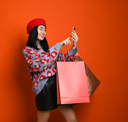Foto de Beautiful young happy Asian woman in a stylish beret and sweater, with a colorful shopping bag using tablet for shopping online. shopping concept. - Imagen libre de derechos