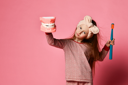 Photo for Red-haired pretty girl in pajamas with a toothbrush and a kissuos mock-up with scales stand over a pink background wall and the joy of a smile on camera. - Royalty Free Image