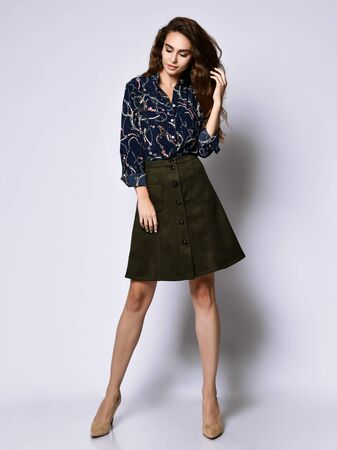 Photo for Vertical of a short beautiful cheerful young woman posing in solitude, in a dark silk blouse with floral patterns, a dark short green skirt with buttons and high-heeled shoes, looking with a smile - Royalty Free Image
