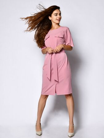 Foto de Young girl in a business dress wearing clothes, pretty smiling on a white background. A slender female model in a pink business dress and white stilettos looks at the camera with smiling. - Imagen libre de derechos