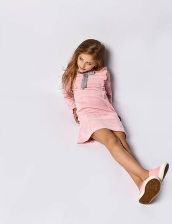 Photo for top view of a teenage girl sitting in a casual pink dress and gym shoes. The style of youth and adolescents. On a light background - Royalty Free Image