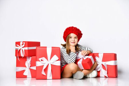 Photo for Portrait of a joyful cute little girl in a red hat sitting in a pile of gift boxes, enjoys the holiday on a light isolated background. - Royalty Free Image
