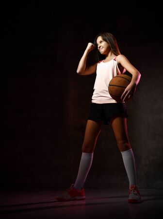 Photo for Portrait of young female basketball player passing the ball. Beautiful caucasian woman in sportswear playing basketball on grey background with copyspace - Royalty Free Image