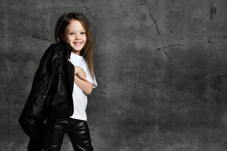 Photo pour Small smiling cute girl in black and white rock star style casual clothing and white sneakers standing over grey concrete background in photo studio. Stylish children clothing concept - image libre de droit
