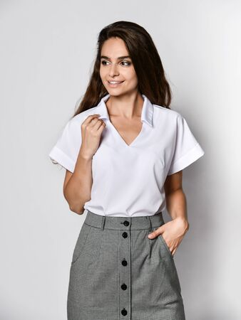 Photo pour Young beautiful woman office manager posing in a new casual white blouse and classic straight dark skirt on a light background. Looking away - image libre de droit