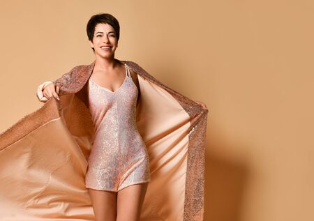 Photo pour middle-aged brunette woman model with short haircut in sexy pink shiny evening costume with mini dress standing over pastel yellow background. Glamorous cocktail clothing, fashion and beauty concept - image libre de droit