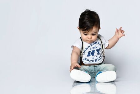 Foto de Little child in t-shirt with inscriptions, jeans with suspenders and booties. He is looking wondered, sitting on floor isolated on white. Articles about childhood or advertising for babies. Close up - Imagen libre de derechos