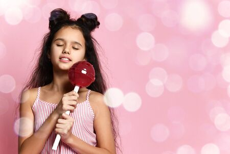 Photo pour Brunette teenage girl with fancy hairstyle, in striped dress. She is smiling with closed eyes, holding a huge red lollipop while posing on pink studio background with bokeh. Fashion, beauty, sweets. Close up - image libre de droit