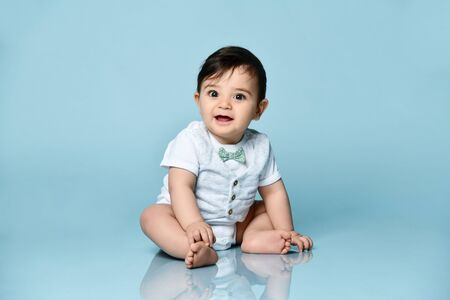 Foto de Baby boy in white bodysuit as a vest with bow-tie, barefoot. He is smiling, sitting on floor against blue studio background. Concept for articles about childhood or advertising for babies. Close up - Imagen libre de derechos