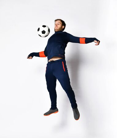 Photo for Young man soccer player in blue sportswear and colored sneakers. He is jumping up, performing tricks with ball, posing isolated on white. Concept of sport, balance and agility. Full-length, copy space - Royalty Free Image