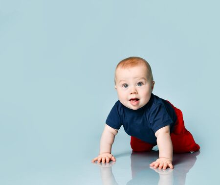 Photo pour Little chubby child in t-shirt and red shorts. He is creeping on the floor against blue background. Concept for articles about childhood, advertising for babies. Close up, copy space - image libre de droit