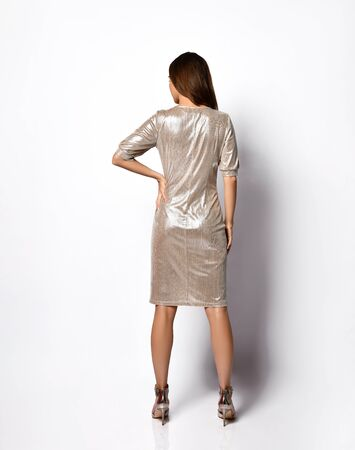 Photo pour Rear view of an elegant beautiful model in a sparkling short silver dress with sleeves to the elbows. Women's fashion, charm and beauty, stylish image, femininity. Full length shot isolated on white. - image libre de droit