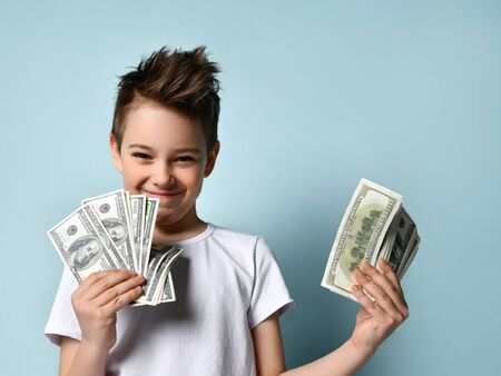 Photo pour Brunet teenage male with stylish haircut in white t-shirt. He is smiling, holding a lot of hundred dollar bills, posing against blue background. Adolescence, fashion, money. Close up, copy space - image libre de droit