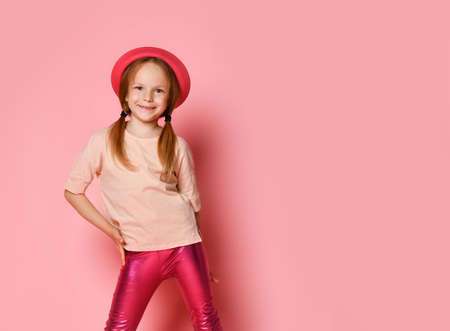 Foto per Stylish cute girl in a pink hat and leggings smiling, holding one hand on her hip with arms on a pink background - Immagine Royalty Free