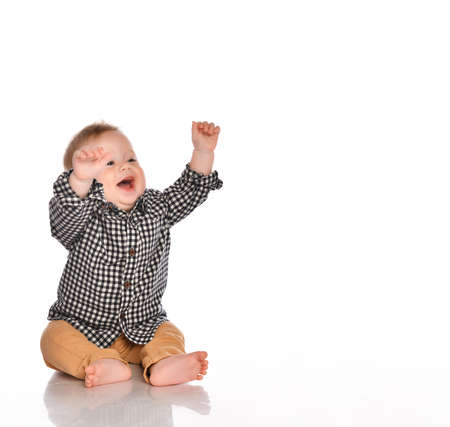 Photo for little boy in a black and white plaid shirt and beige pants raises his hands up and smiles directly into the camera in the studio on a white background. Child development concept - Royalty Free Image