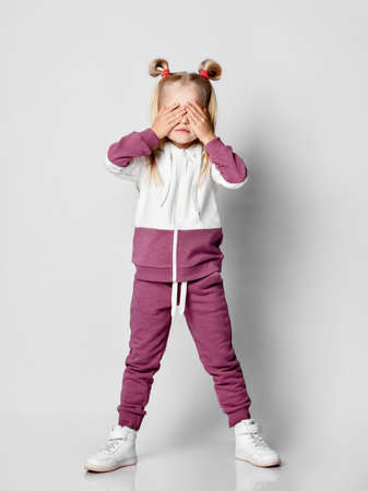 Photo pour little blonde covered her face with her hands with her palms, dressed in a fashionable tracksuit, posing in the studio on a gray background. The child touches his face in surprise. - image libre de droit