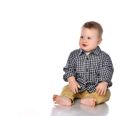 Foto de Portrait of a little one-year-old boy on a white background. The boy sits in a shirt and shorts with tears in his eyes. The boy is capricious because his toy was taken away. The concept of children's whims. - Imagen libre de derechos
