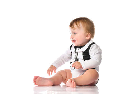 Photo pour boy toddler portrait with blue eyes dressed in black and white bodysuit. The child is sitting barefoot and smiling happily on a white background with space for text. - image libre de droit