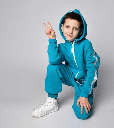 Boy in warm sportswear kneeing gesturing victory