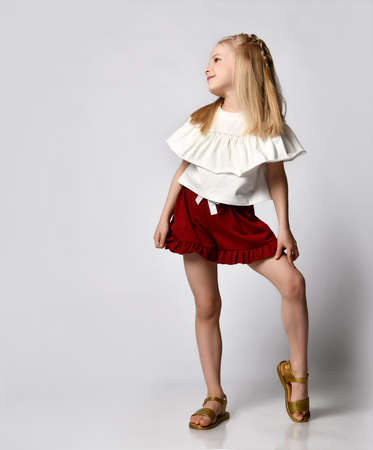 Photo pour cute smiling little girl in a white blouse with ruffles, burgundy shorts and sandals, put her leg to the side - image libre de droit