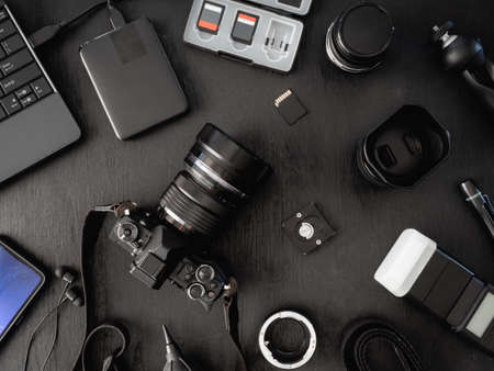 Photo pour top view of work space photographer with digital camera, flash, cleaning kit, memory card, external harddisk, USB card reader, laptop and camera accessory on black table background - image libre de droit