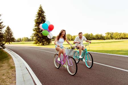 Photo pour positive happy couple in love ride bicycles have fun - image libre de droit