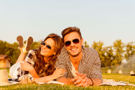 Photo pour lovers lying on the grass with glasses - image libre de droit