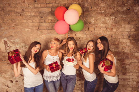 Funny pretty girls holding birthday cake, balloons and presents