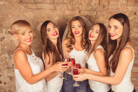 Cute young women wearing dress code celebrating hen-party with sparkling wine