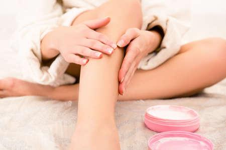 Foto de Closeup photo of young woman smearing cream on her leg - Imagen libre de derechos
