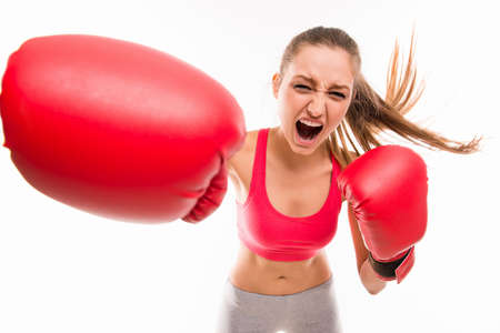 Beautiful angry sportswoman in red boxing gloves