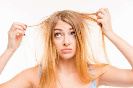 Photo for Sad girl looking at her damaged hair - Royalty Free Image
