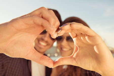 Photo pour Happy romantic couple in love gesturing a heart with fingers - image libre de droit