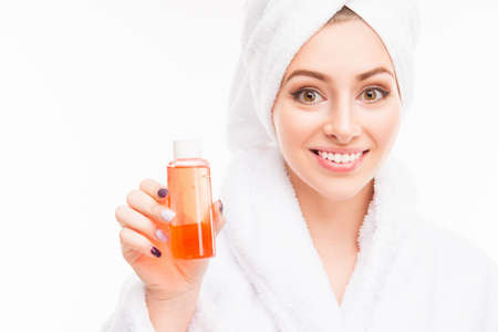 Photo pour Pretty girl with towel on her head holding shampoo - image libre de droit