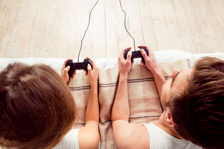 Photo pour Happy couple in love playing video games with joysticks on the bed - image libre de droit