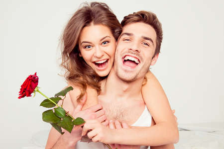 Foto de Cheerful young man and woman in love hugging in the bedroom with rose - Imagen libre de derechos