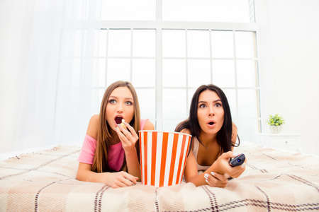 Wow! Two excited girls watching film and eating popcorn