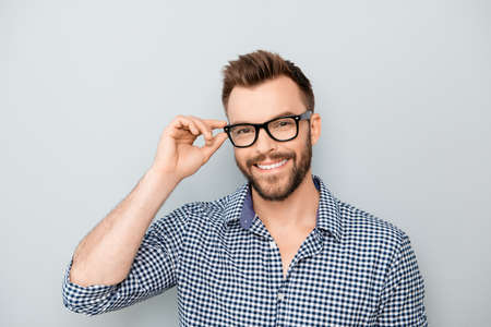 Cheerful smiling young businessman touching his glasses