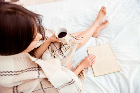 Photo for Top view of young woman reading book and basking with plaid and coffee - Royalty Free Image
