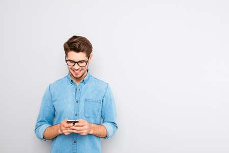 Foto de Happy man in glasses typing sms on gray background - Imagen libre de derechos