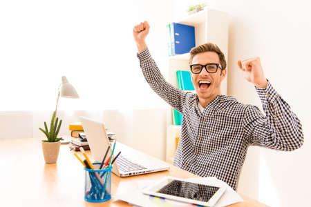 Photo pour Portrait of happy successful young worker with raised hands - image libre de droit
