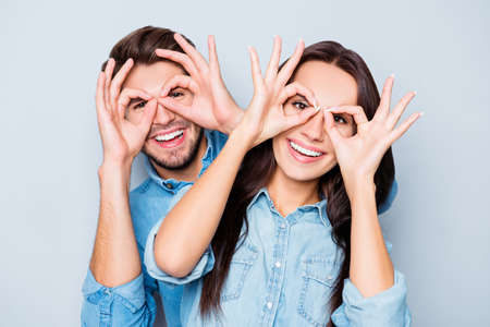 Cheerful happy couple in love having fun and holding fingers near eyes