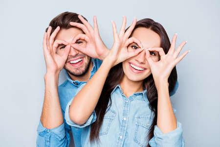 Foto de Cheerful happy couple in love having fun and holding fingers near eyes - Imagen libre de derechos