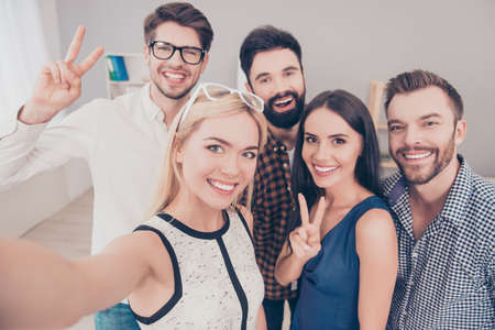 Photo pour Group of happy smiling businesspeople making selfie and gesturing - image libre de droit