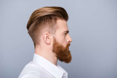 Photo pour Side view portrait of confident bearded man with beautiful hairstyle   in white shirt looking on copy space - image libre de droit