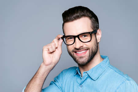 Photo pour Portrait of young smiling manager in jeans shirt touching his glasses isolated on gray background - image libre de droit