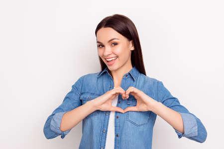 Foto de Cute beautiful girl in love making heart with fingers and smiling - Imagen libre de derechos