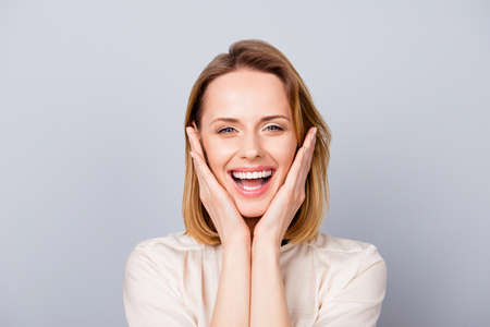Photo pour Close up portrait of funny cute young woman laughing and touching her cheeks - image libre de droit